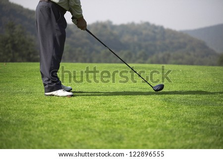 Low section of male golf player ready to hit the ball - stock photo