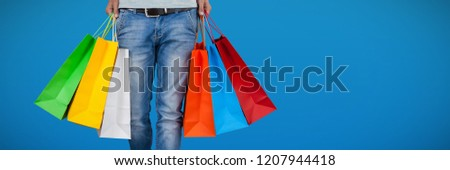Low section of man carrying colorful shopping bag against abstract blue background #1207944418