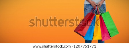 Low section of man carrying colorful shopping bag standing against white background against abstract saffron background #1207951771