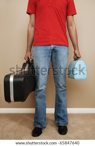 Low section of man carrying lunchbox and guitar