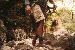 Low section of man in trekking gear walking through rocky trail. Man hiking through rocky mountain trail.