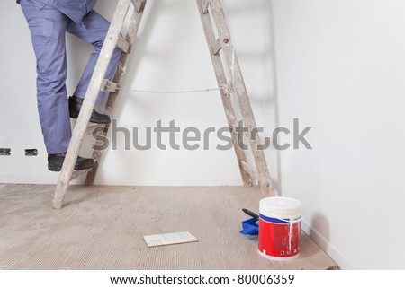 Low section of man's legs climbing wooden ladder - stock photo