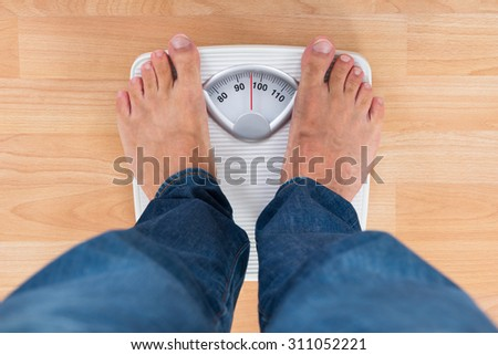 Low Section Of Man Standing On Weighing Scale