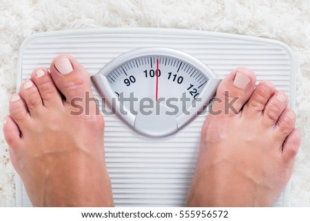 Low Section Of Overweight Obese Person Measuring Body Weight On Weighing Scale