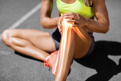 Low section of sportswoman suffering from knee pain while sitting on track during sunny day