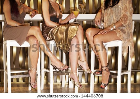Low section of three stylishly dressed women sitting legs crossed at the bar