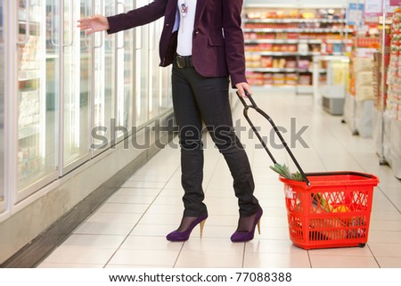 Low section of woman in front of refrigerator carrying basket in the supermarket