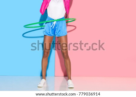 low section of  woman posing while exersizing with hoop on pink and blue background   #779036914
