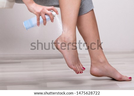 Low Section Of Woman's Hand Spraying Relief Spray On Her Foot At Home #1475628722