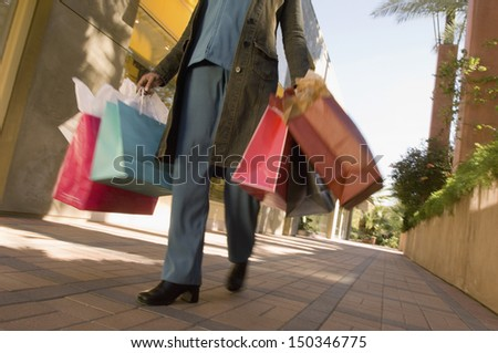 Low section of woman with shopping bags walking on pavement