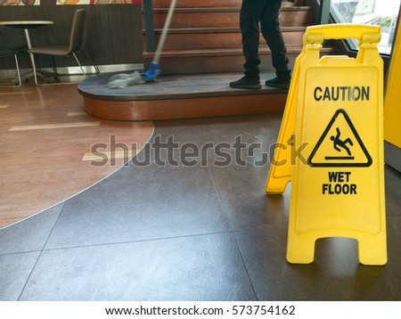 Low Section Of Worker Mopping Floor With Wet Floor Caution Sign On Floor   #573754162