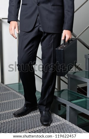 Low section of young businessman carrying briefcase by steps
