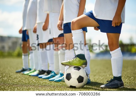 Low section portrait of junior football team : legs of boys standing in row with captain stepping on ball in foreground #708003286