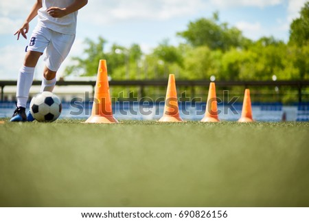 Low section portrait of unrecognizable boy running in football field leading ball between row of orange cones during practice