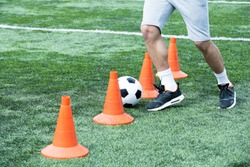 Low section portrait of unrecognizable muscular man leading ball between orange cones during football practice, copy space