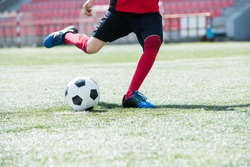 Low section portrait of unrecognizable teenage boy kicking ball playing football on stadium during practice, copy space