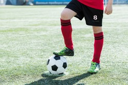 Low section portrait of unrecognizable teenage boy standing on football field and stepping on ball, copy space