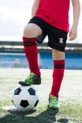 Low section portrait of unrecognizable teenage boy wearing red uniform standing on football field and stepping on ball