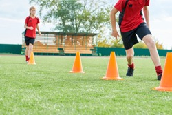 Low section portrait of unrecognizable teenage boys running between orange cones during football practice outdoors, copy space