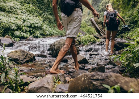Low section shot of man and woman crossing the stream barefooted. Couple walking by the creek in forest with their shoes in hand. Hikers hiking in forest.