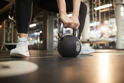 Low section view at unrecognizable young woman picking up dumbbell during strength workout in modern gym, copy spaceLow section view at unrecognizable young woman picking up dumbbell during strength