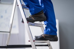 Low Section View Of A Handyman's Foot Climbing Ladder