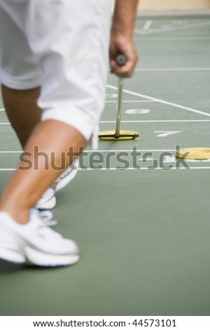 Low section view of a senior woman playing shuffleboard