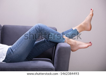 Low Section View Of A Woman Relaxing On Sofa