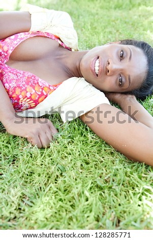 "Low side view of a beautiful ""african american"" woman laying down on green grass while on a summer vacation, smiling at the camera."