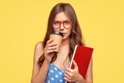 Low spirited young female student feels sad after recieving bad mark for exam, being tired, drinks hot coffee, holds scientific literature, stands against yellow background. Youth, studying concept