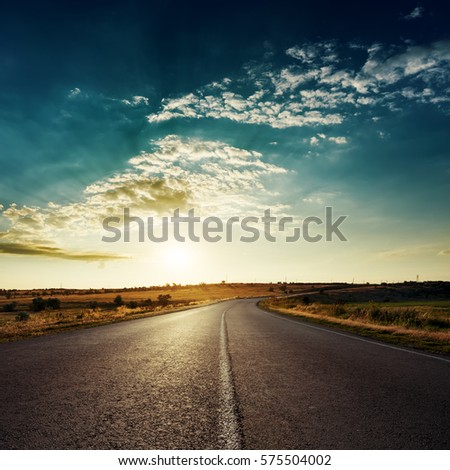 low sun in dramatic clouds over asphalt road, sunset time #575504002