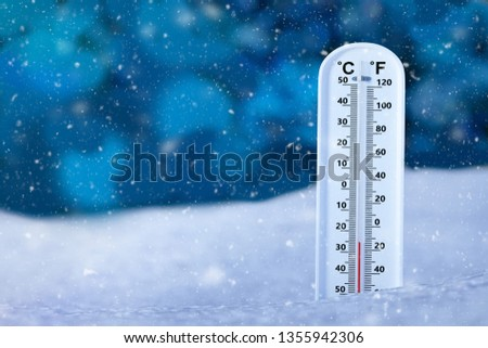 Low temperature show on thermometer on snow ground, weather temperature on snowing day