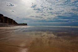 Low tide at sandy beach with rock cliffs. Shining sand surface reflecting cloudy sky. Normandy, France, Europe.