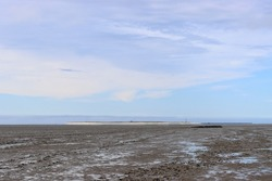 Low tide in the Wadden Sea of the North Sea near Schillig with a view of the East Frisian island of Minsener Oog in Germany with a blue cloudy sky in a tranquil scene