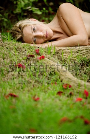 Low view of a beautiful blonde woman laying naked on green grass and tree roots, covered in red rose petals.