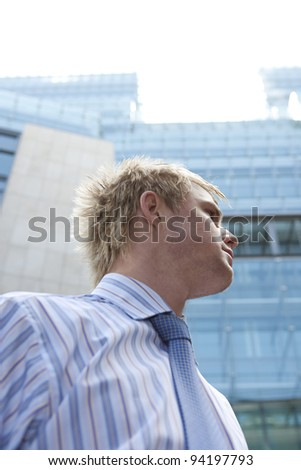 Low view of a businessman standing by office buildings in the city.
