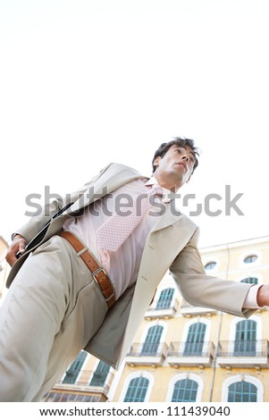 Low view of a young businessman running through a classic office buildings square with a blue sky behind him.