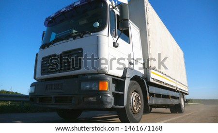 Low view of truck with cargo trailer driving on highway and transporting goods. Lorry riding through countryside at sunny day. Transport and logistic concept. Slow motion Close up #1461671168