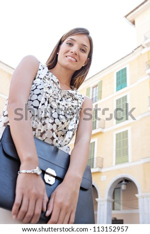 Low view portrait of a young businesswoman holding a black folder while standing in front of classic buildings in the city, smiling.