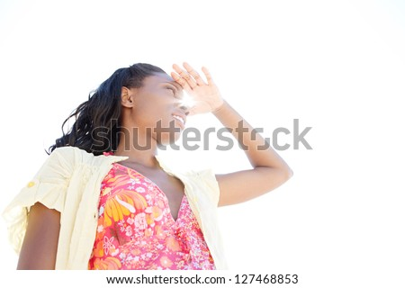 Low view portrait of an attractive black woman on holiday shading her eyes with her hand against a clean sky, with sun rays filtering trough.