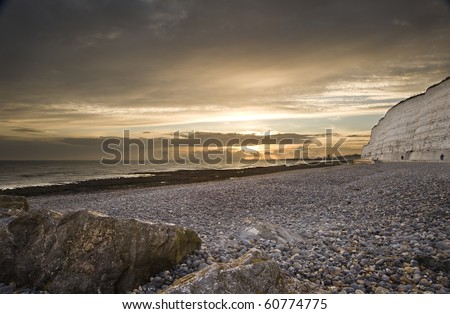 Low viewpoint along stony beach with rocks and white cliffs into golden sunset