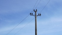 low voltage electricity post against blue background