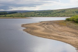 Low water level on a UK reservoir. Fly fishing in drought conditions. Water shortage during summer.