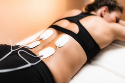 Lower Back Physical Therapy with TENS Electrode Pads, Transcutaneous Electrical Nerve Stimulation. Electrodes onto Patient's Lower Back