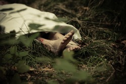 Lower body of abandoned murder victim in dark countryside with bare feet protruding