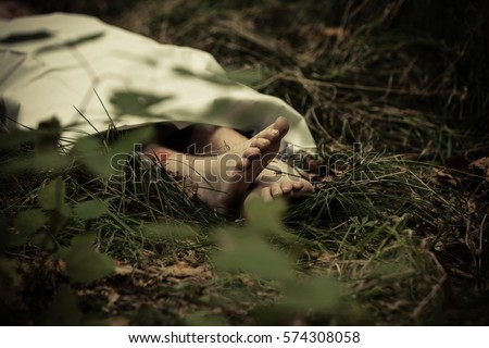 Lower body of abandoned murder victim in dark countryside with bare feet protruding Stockfoto ©