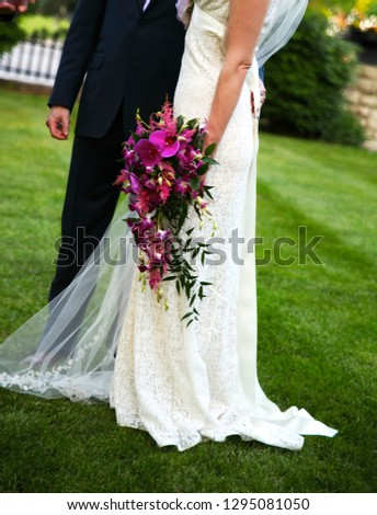 Lower body of bride and groom together outside on green grass lawn, with bride carrying cascading fuchsia pink orchids and wearing vintage style lace wedding dress