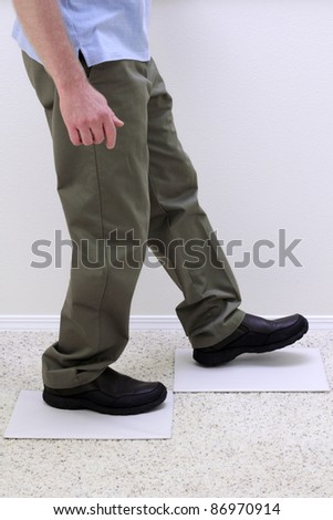 Lower body of relaxed man walking over two light gray empty paper boards.