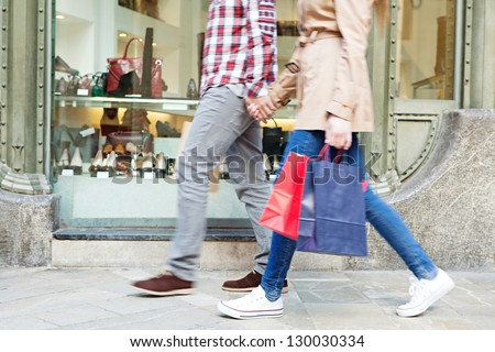 Lower body section of a young tourist couple walking by store windows and holding paper shopping bags in a destination city.