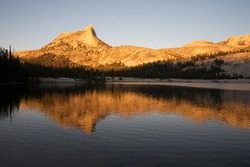 Lower Cathedral Lake in Yosemite National Park on the John Muir Trail. Alpine Glow and reflection on the lake.